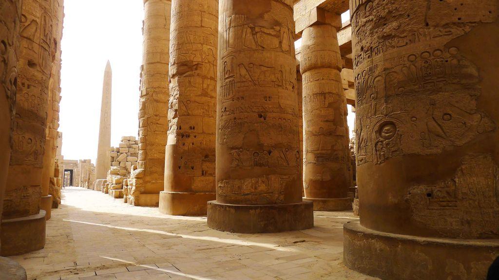 Allée de colonnes de pierre avec au fond l'obélisque